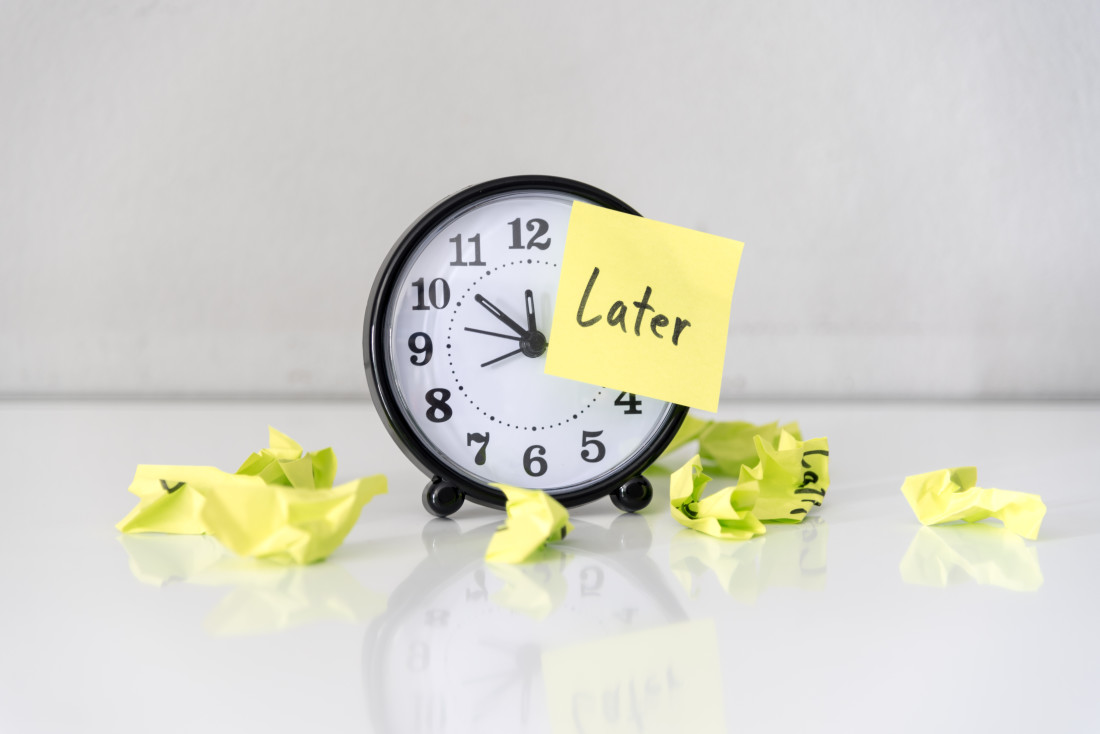 "Alarm Clock with sticky note saying ""Later"" on its face"