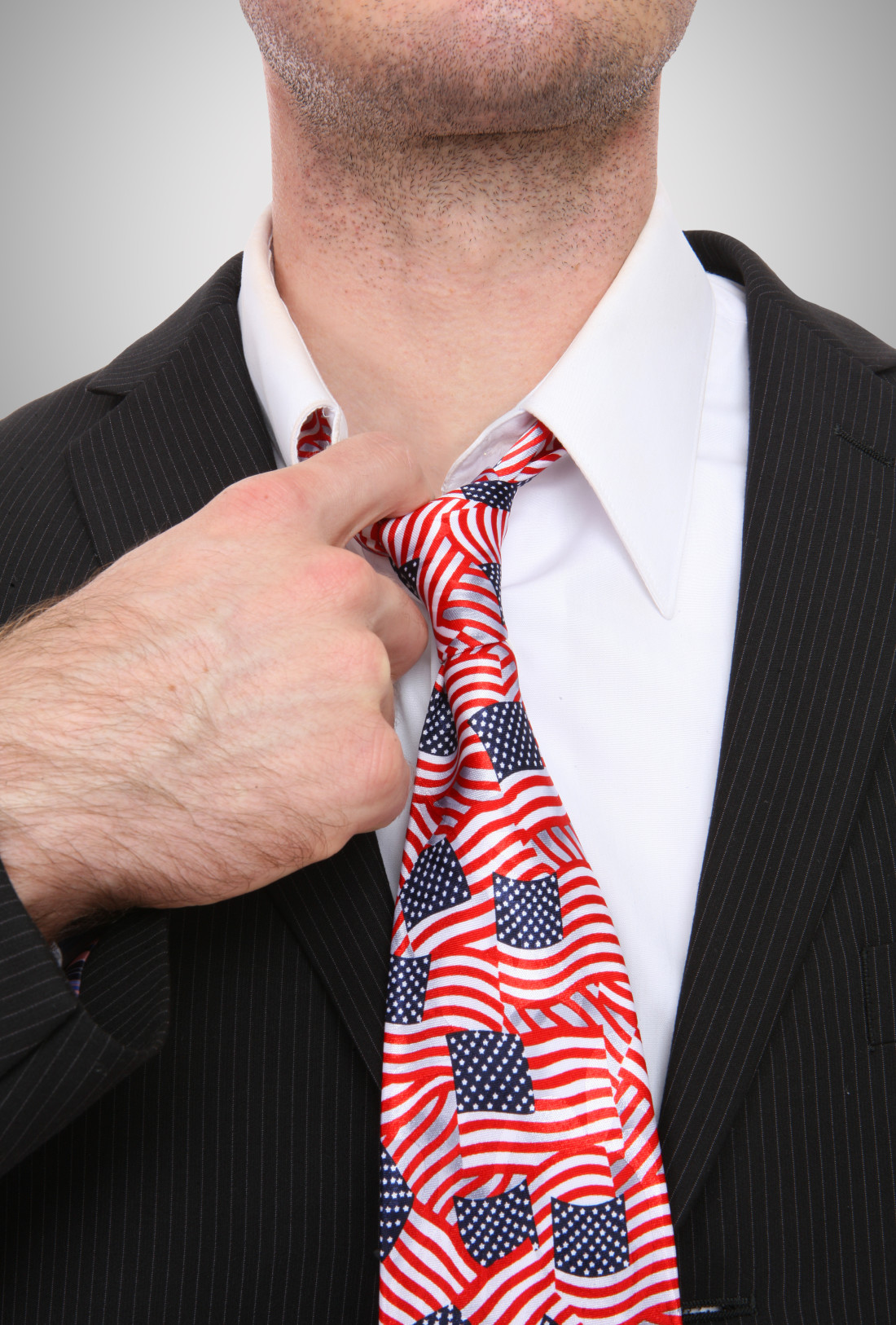 Image of person in suit wearing a neck tie with American Flag print