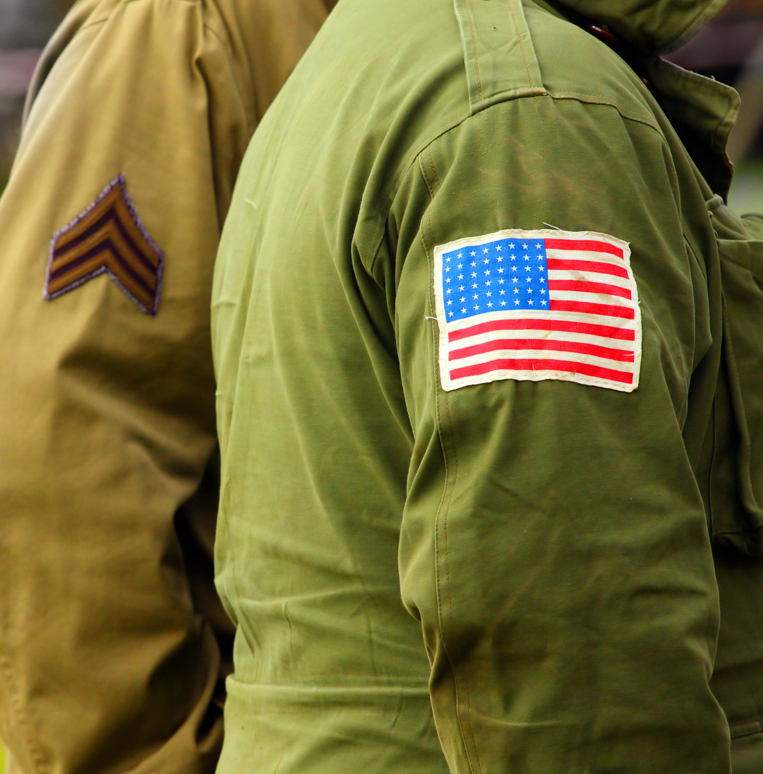 Image of two figures in US Army Jackets, one which has an American Flag patch sewn to the arm