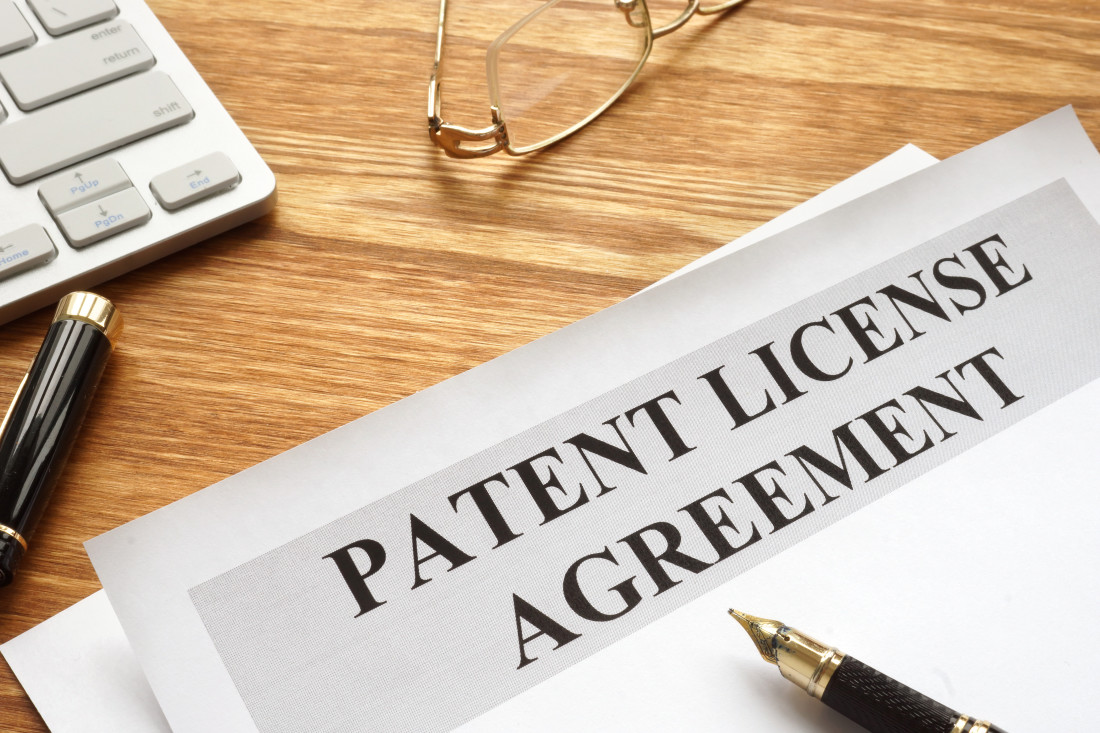 Patent License Agreement Heading with pens, eyeglasses and a calculator on a table