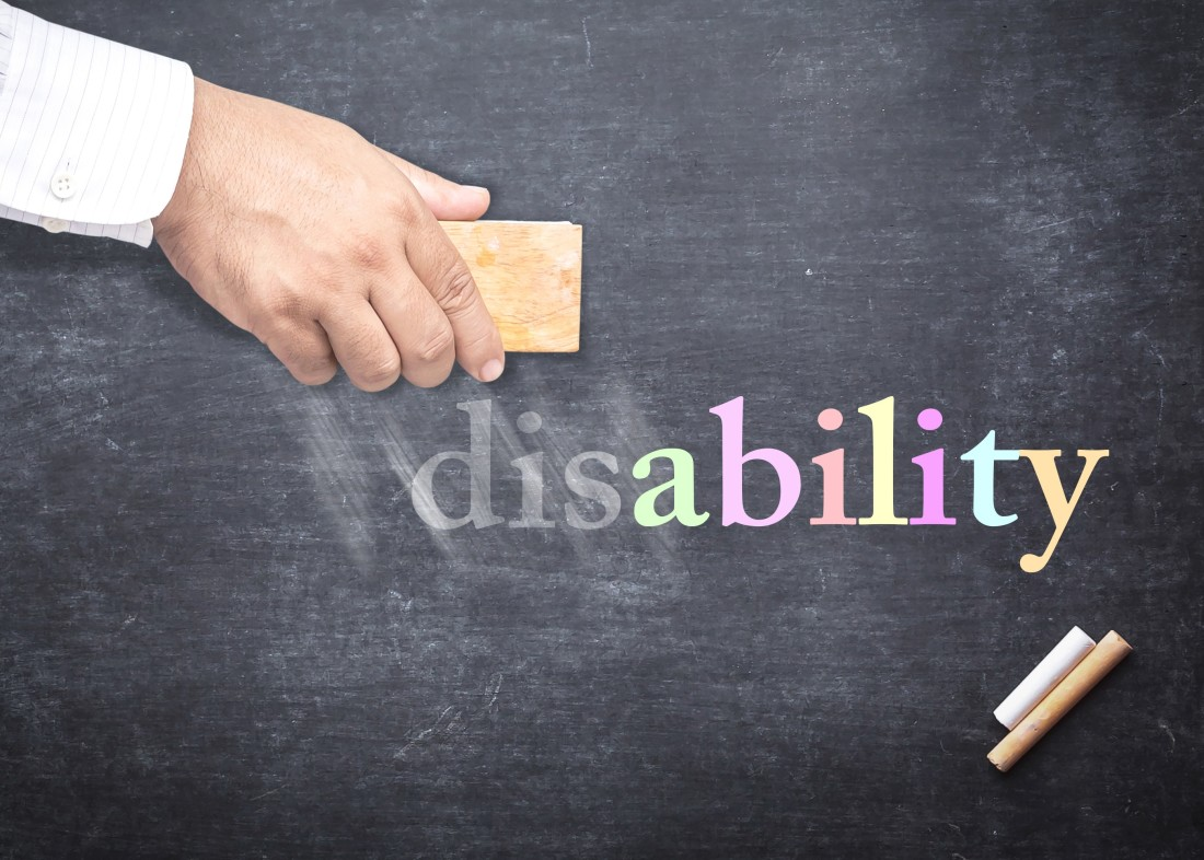"hand holding an eraser changing word ""disability"" to ""ability"" on a chalk board"